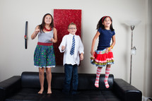 siblings jumping on a couch