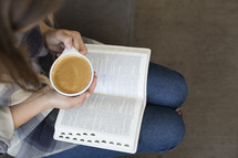woman with a Bible in her lap and a cup of latte