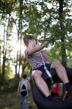Teen boy swinging on a tire suspended from a tree.