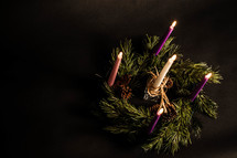 Aerial view of five lit candles in pine wreath with pine cones.