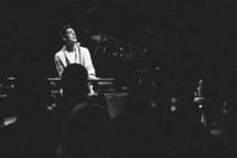 man singing on stage while playing a keyboard