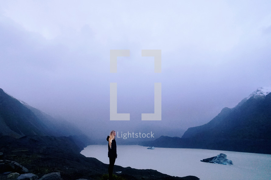 a woman standing by a mountain lake in fog