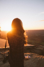 woman with a camera standing on a mountaintop