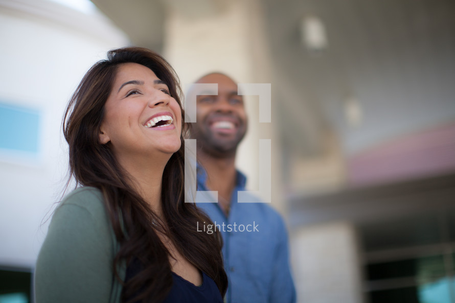 man and woman smiling standing outdoors under a covered walkway
