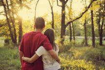 Couple standing in a forest at sunrise.