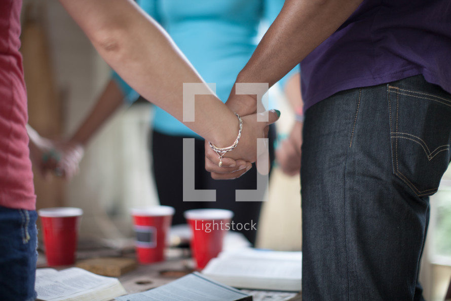 holding hands in prayer circle above open Bibles