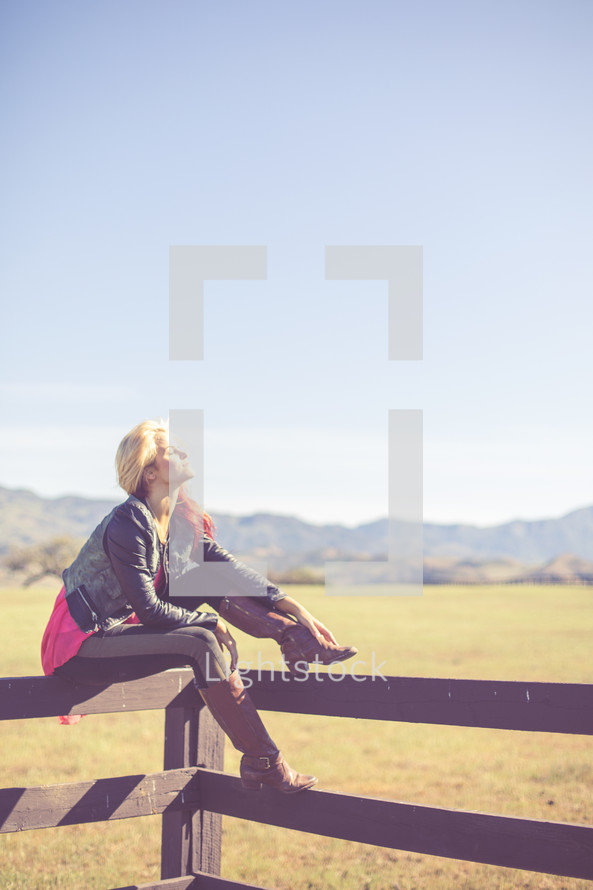 Woman sitting and balancing on a fence rail in a pasture with mountains.