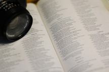 a camera resting on the pages of a Bible