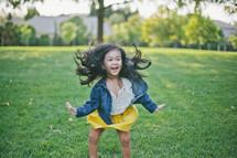 A little girl dancing and twirling in a field of grass.