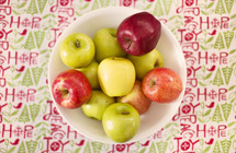 red and green apples in a bowl and Christmas table cloth