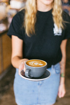 woman holding cappuccino in a mug