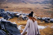 woman in a sweater walking on rocks on a mountain