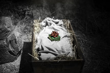Green warpped box with red bow lying on linen cloth in hay-filled basket.