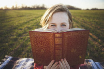 Girl sitting on blanket in grassy field reading ornate William Shakespeare book.