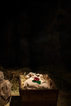Green wrapped box with red bow on linen cloth in hay-filled basket at night.