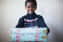a boy child holding a wrapped Christmas girt