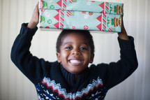 a boy child holding a Christmas present over his head