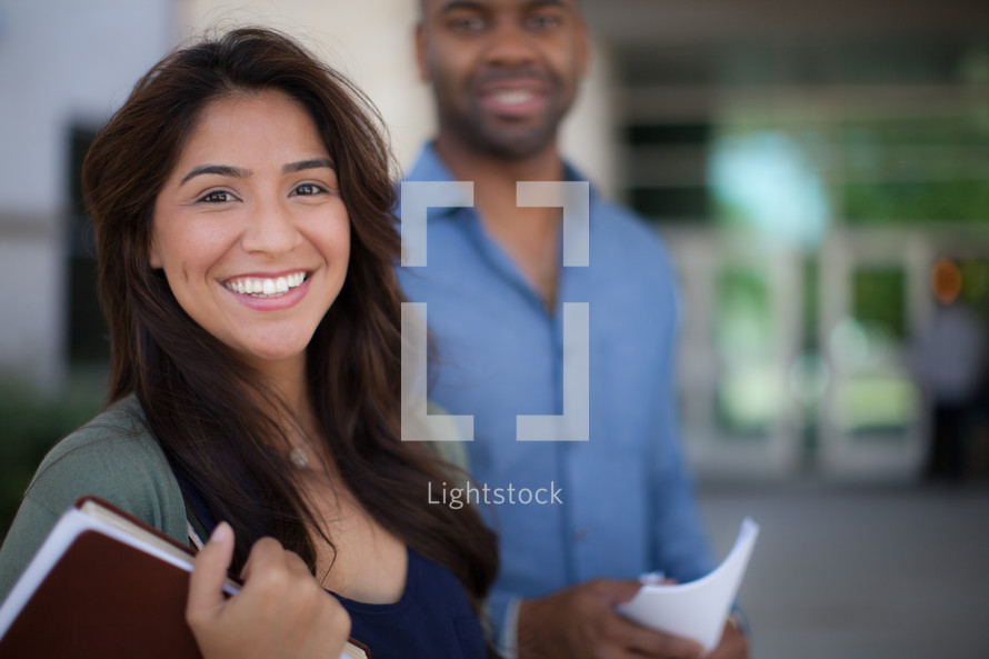 smiling man and woman holding Bibles