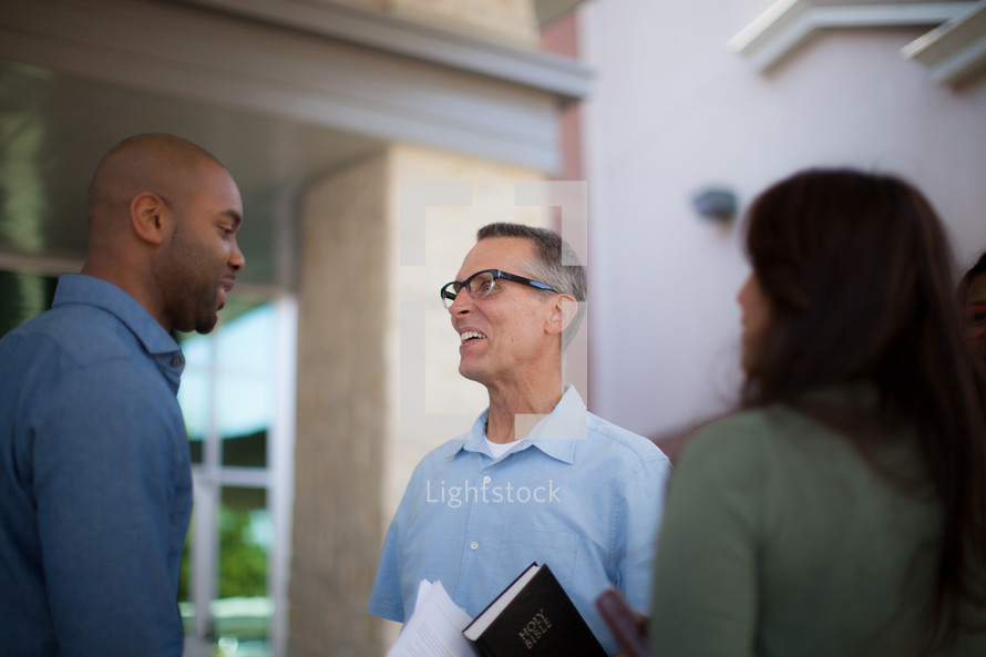 greeters welcoming people at the entrance of a church