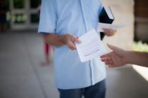 greeter handing out church bulletins