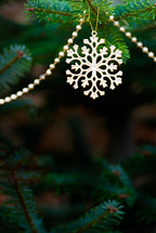 a snowflake ornament and beads on a Christmas tree
