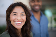 smiling man and woman standing outdoors