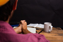 man with praying hands over a journal and an open Bible