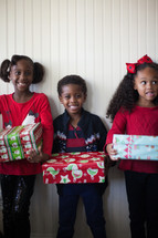siblings holding wrapped Christmas gifts