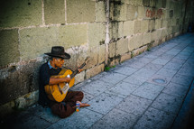 An old man playing a guitar on a stone sidewalk.