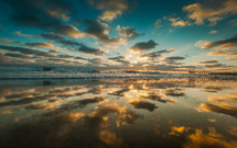 reflection of clouds on the ocean at sunrise