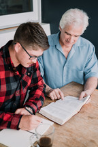 mentor reading a Bible with a man at a Bible study