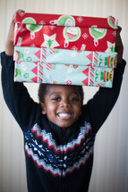a boy child holding wrapped Christmas gifts over his head