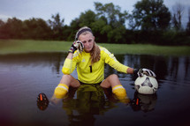 Girl sitting in a pool of water with a soccer ball.