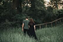 a couple walking through tall grasses