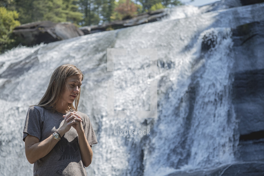 praying in front of a waterfall in Asheville, NC