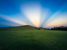 radiating sunlight behind a hill