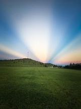 sunbeams behind a hill