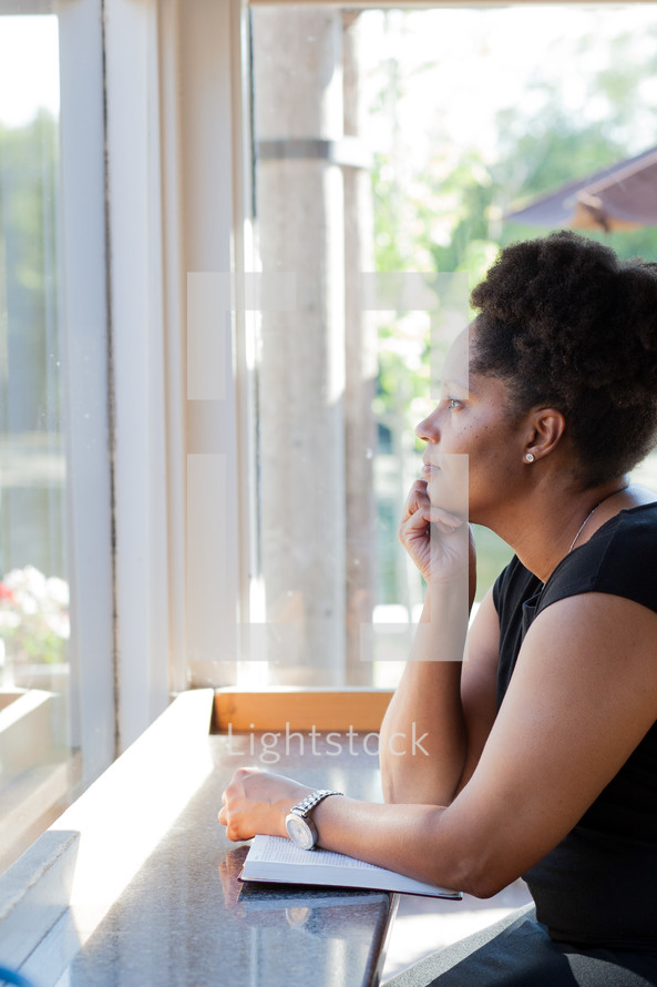 a woman with a Bible looking out a window
