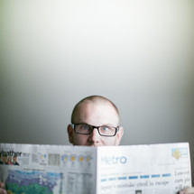 man wearing glasses reading the newspaper amazed by a story of Good news