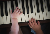 infant and toddler hands on a piano