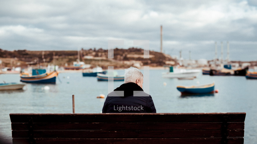 a man sitting on a bench looking out at the boats