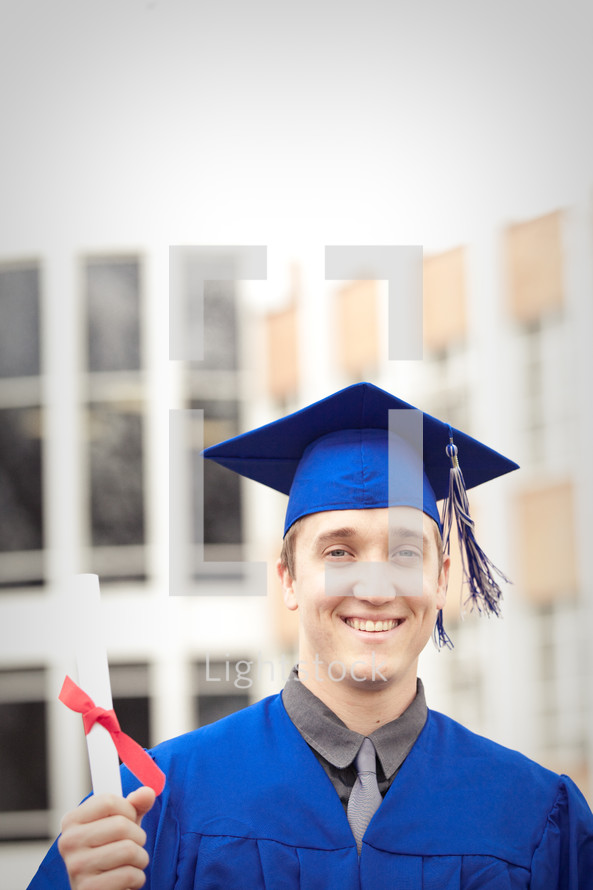 Smiling graduate with diploma.