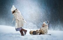 a girl pulling a boy on a sled