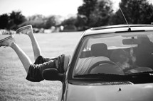 teen boy with his feet hanging out of a car window