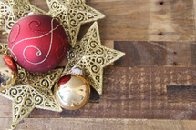 Christmas ornaments, stars and baubles on a wood floor background