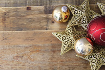 Christmas ornaments, stars and baubles, on a wood floor background