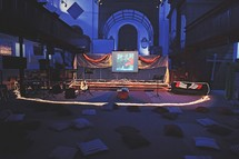 pillows on the floor and a stage set up for a youth rally presentation