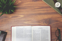 open Bible and reading glasses on a wood table - James
