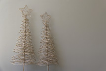 Gold wire Christmas trees against a grey background