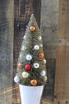 Small decorated Christmas tree against a wooden background